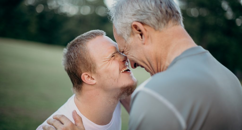 Un jeune homme trisomique sourit, le front collé sur celui de son père, un homme aux cheveux gris.