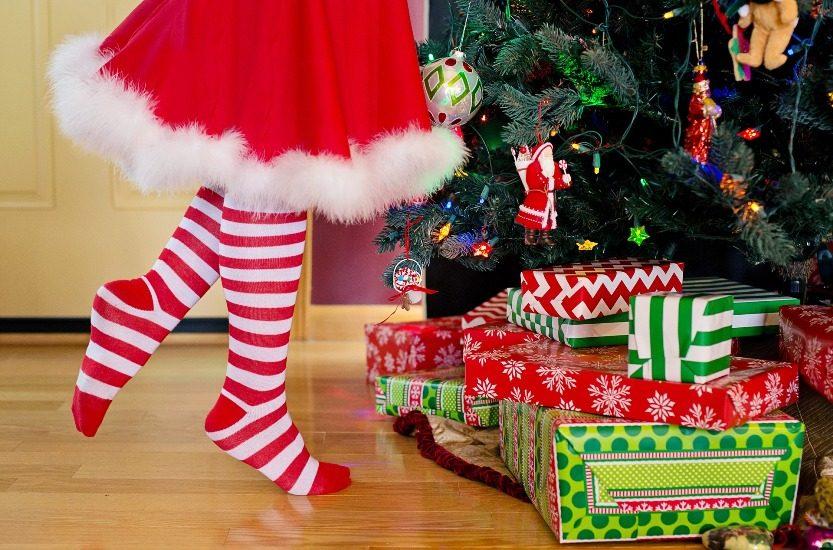 On aperçoit le bas d'une jupe  rouge avec un rebord de fourrure blanche et des jambes qui portes des bas rayés rouge et blanc. À côté, des cadeaux emballés au pied d'un sapin de Noel.