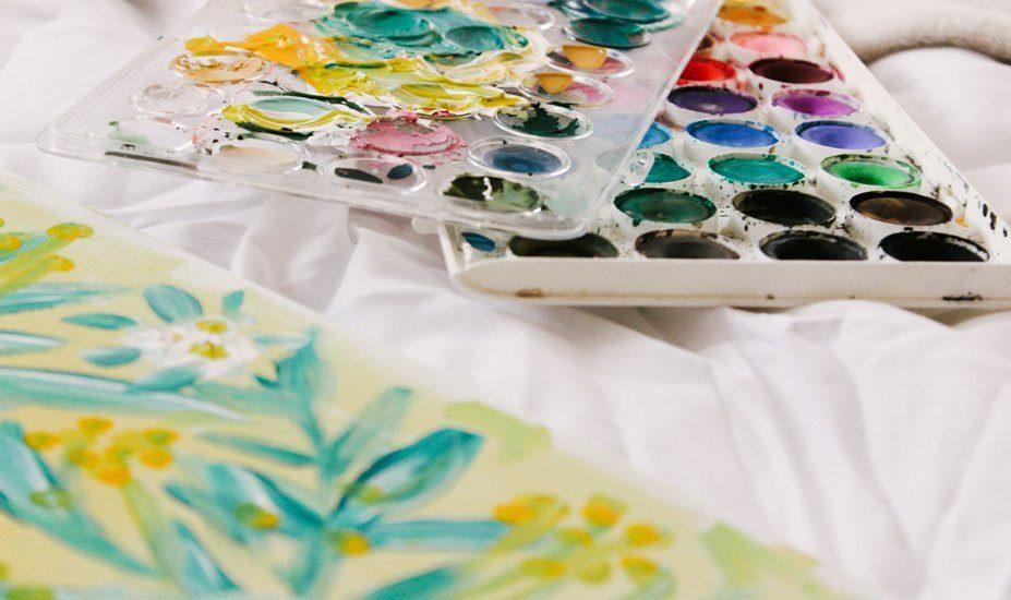 On aperçoit deux palettes de couleurs pour peintre et une toile sur laquelle des fleurs sont peintes.