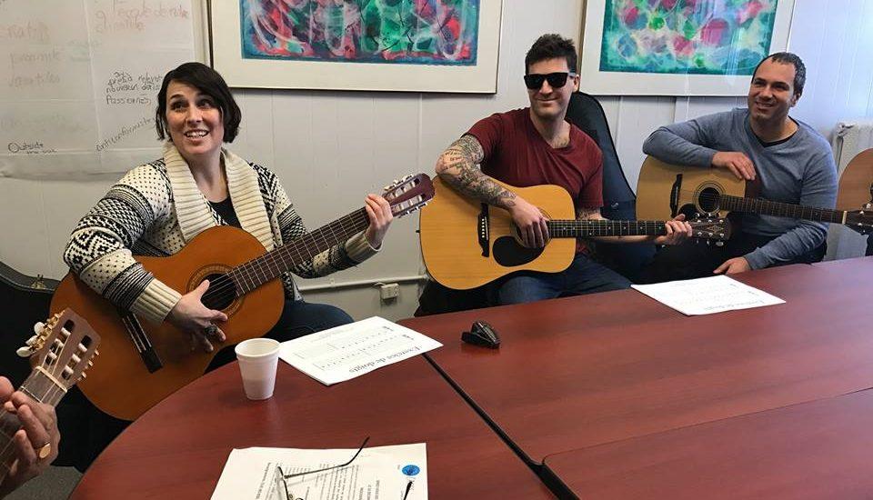 Photo prise lors d'un des cours. On voit trois personnes autour d'une table avec chacun une guitare.