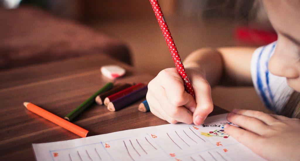 une main d'enfant écrit avec un crayon à mine sur une feuille d'exercices.
