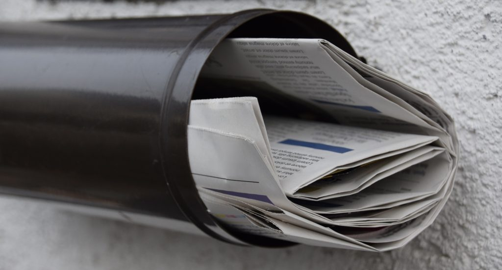 Un journal roulé dans une boîte aux lettres cylindrique.