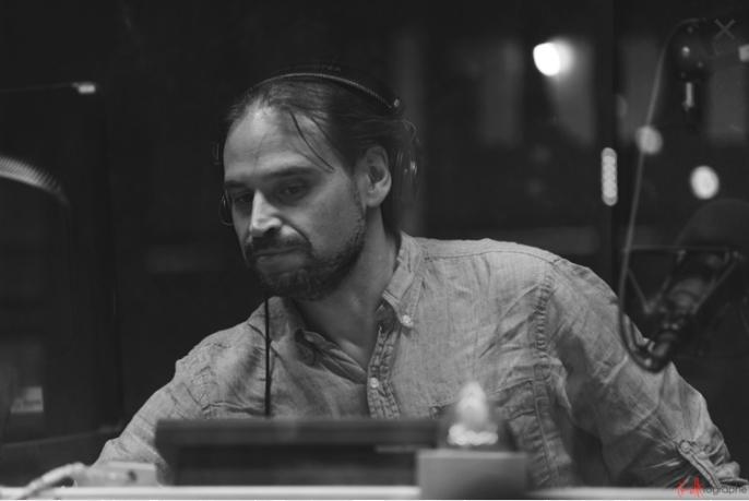 Photo en noir et blanc de l'animateur Marc Bolduc, en train de s'occuper de la technique de son émission. Il a les cheveux bruns foncés et des écouteurs sur la tête.