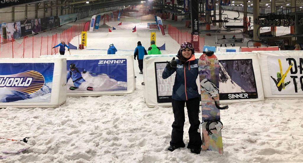 Sandrine pose avec son snowboard au pied de la piste enneigée.