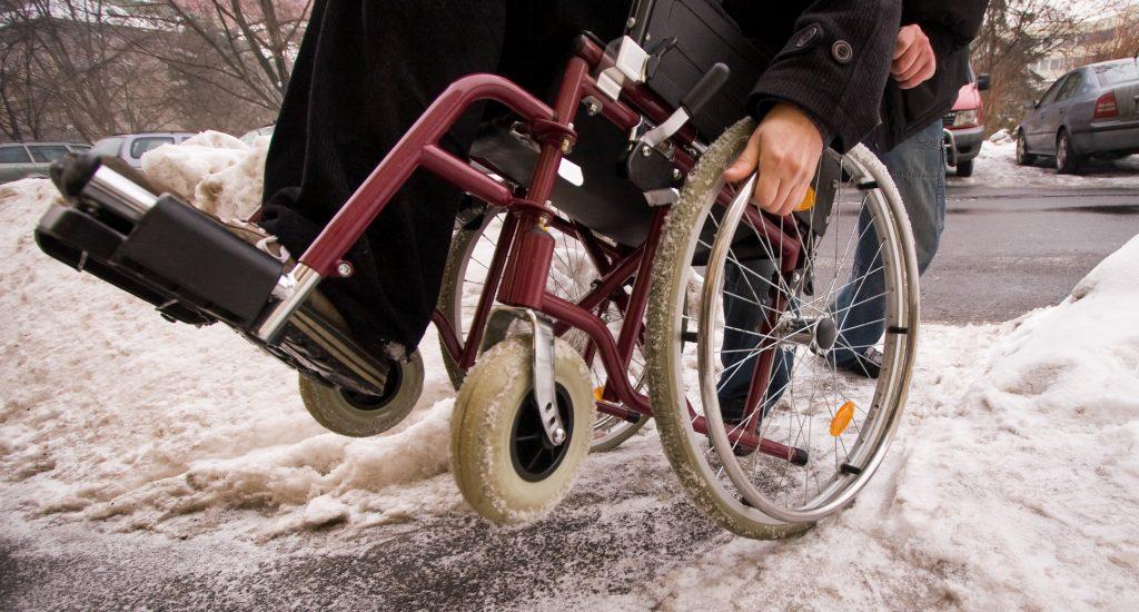 Quelqu'un pousse une personne en fauteuil roulant pour l'aider à monter un un trottoir enneigé.