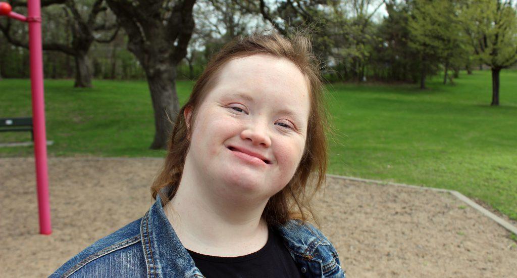 Une jeune femme, ayant la trisomie 21, affiche un beau sourire. Elle est dans un parc.