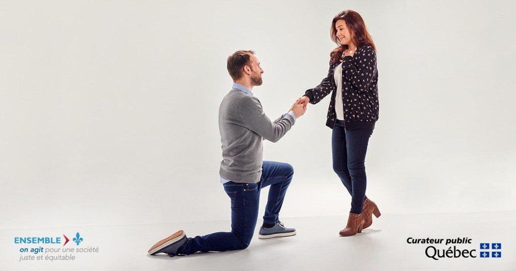 Une homme est à genoux et tiens dans ses mains la main d'une jeune femme , comme pour une demande en mariage.