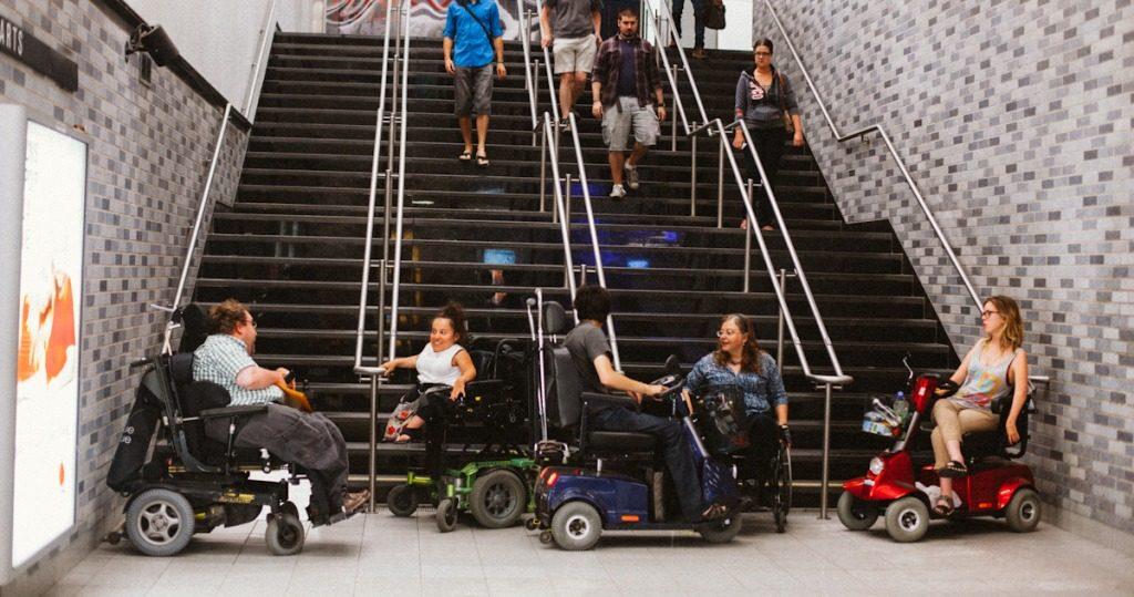 Des personnes en fauteuil roulant bloquent l'accès aux escaliers d'une station de métro qui n'est pas accessible.
