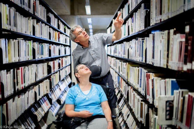 Un homme accompagne une femme en fauteuil roulant dans les rayons de livres de la Grande Bibliothèque.