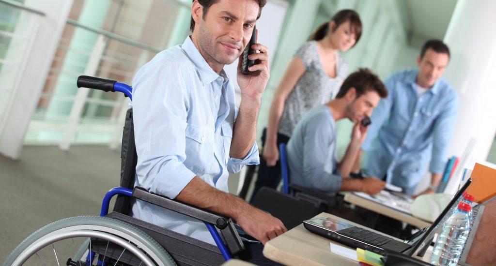 Un homme en fauteuil roulant, portant une chemise blanche, parle au téléphone dans un bureau, devant un ordinateur.