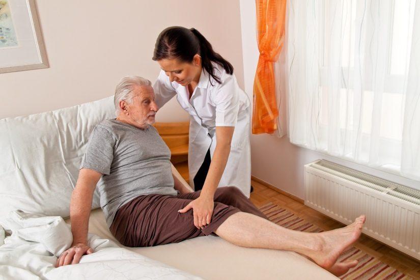 Une femme aide un homme âgé à s'installer dans son lit.