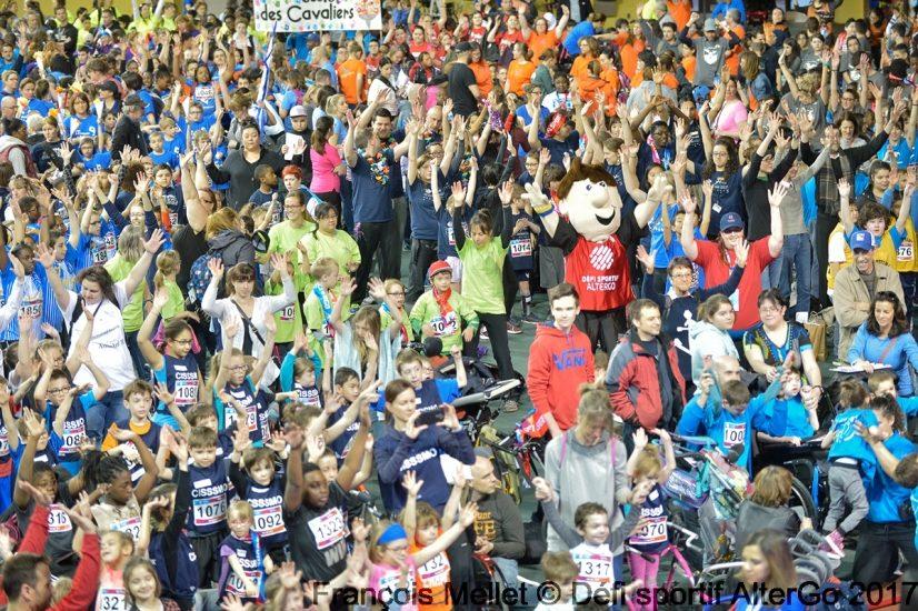 Foule de participants du défi, avec des t-shirts de toutes les couleurs. On voit aussi la mascotte.