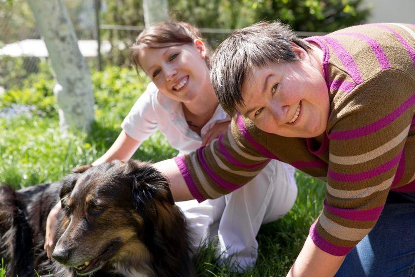 Deux femmes, dont une est trisomique, flattent un chien en regardant vers la caméra