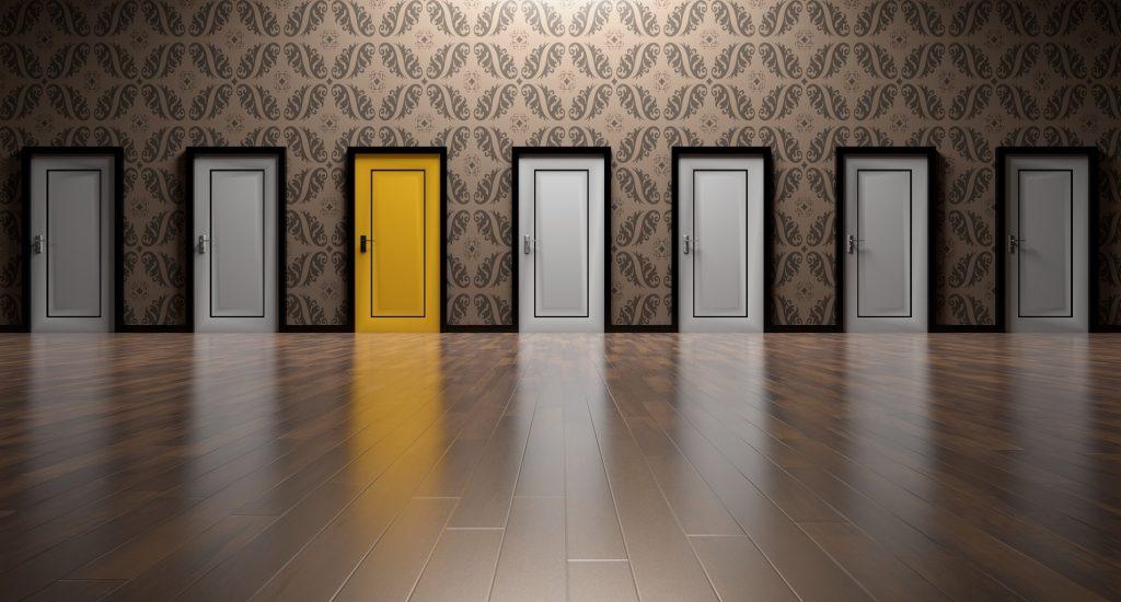 Une séries de portes, toutes blanches, sauf une qui est jaune.