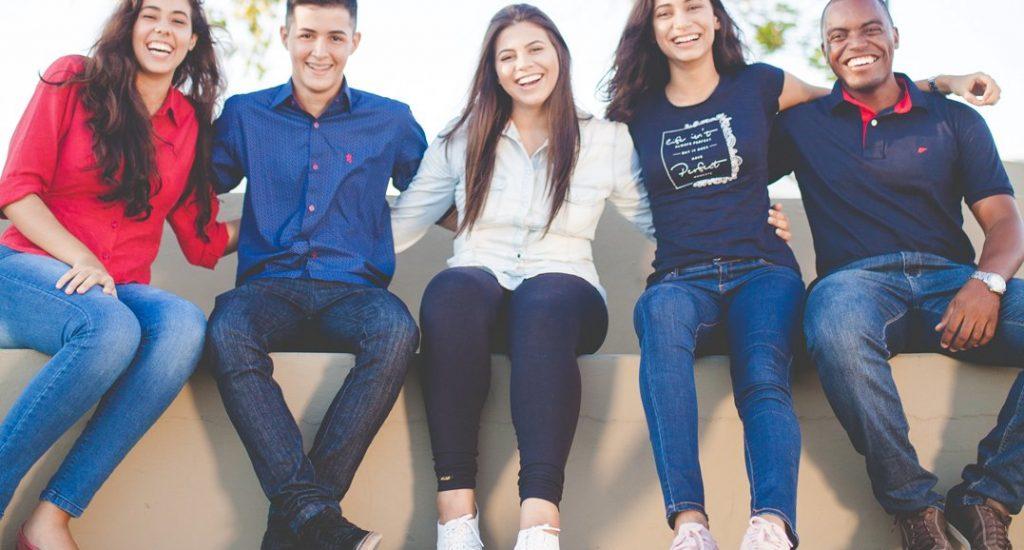 Jeunes adultes souriants (3 femmes et deux hommes).