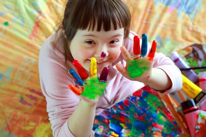 Une jeune fille ayant une trisomie 21 a les mains pleines de gouache et même une petite tache sur le nez.