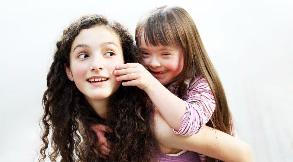 Une jeune fille au long cheveux bruns frisés, tient sur sur son dos une fillette aux cheveux châtains droits qui montre les traits de la trisomie 21.