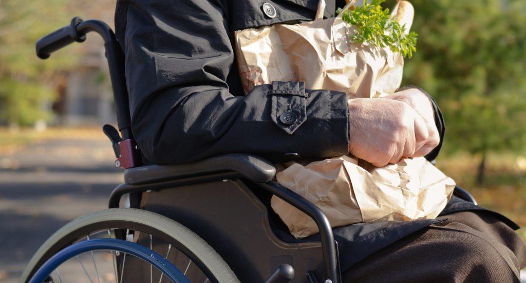 une personne en fauteuil roulant tient dans ses mains un sac d'épicerie.