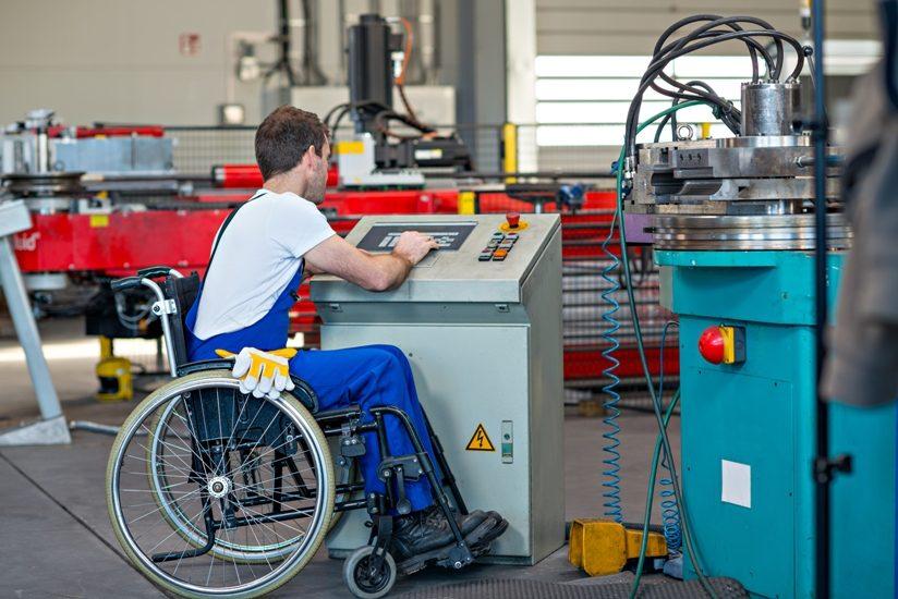 Dans une usine, un homme en fauteuil roulant travaillent à une machine, appuyant sur des boutons.