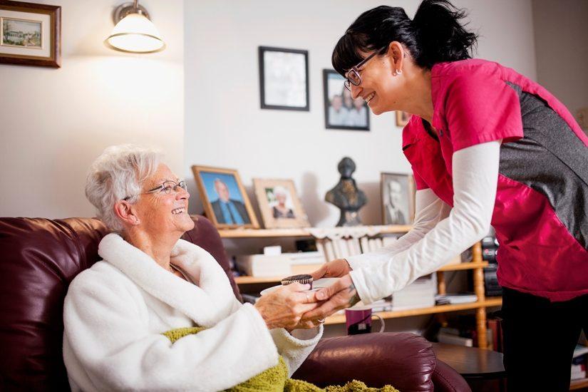 Une préposée de Logisoutien sert un petit gâteau à une dame âgée cheveux blancs, en peignoir) assiste dans un fauteuil.