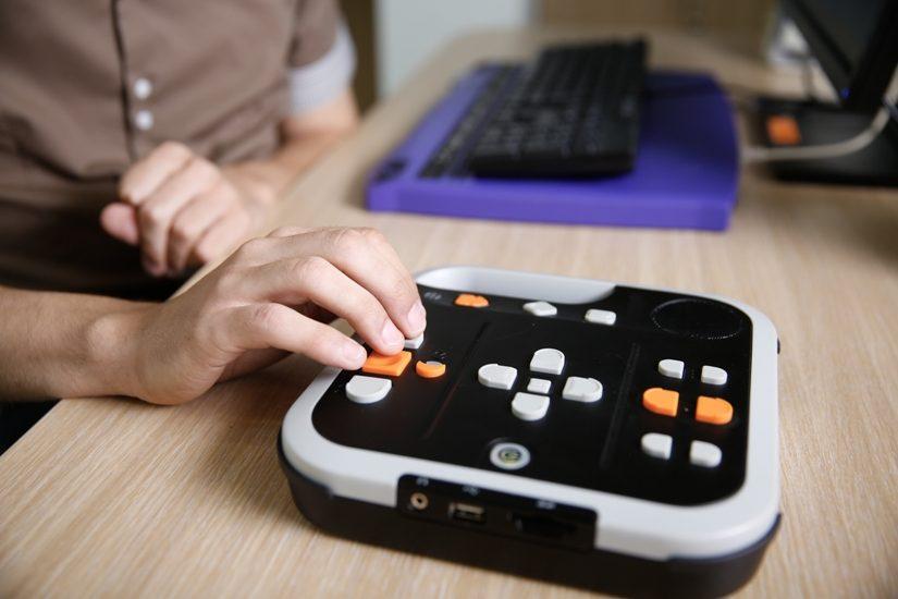 À l'avant plan, un lecteur Victor. Derrière, on voit un clavier d'ordinateur avec clavier braille.