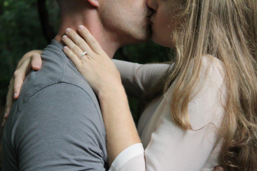 Un très gros plan sur un couple qui s'embrasse, on ne voit pas leurs yeux et le haut de leur tête. La femme est blonde.