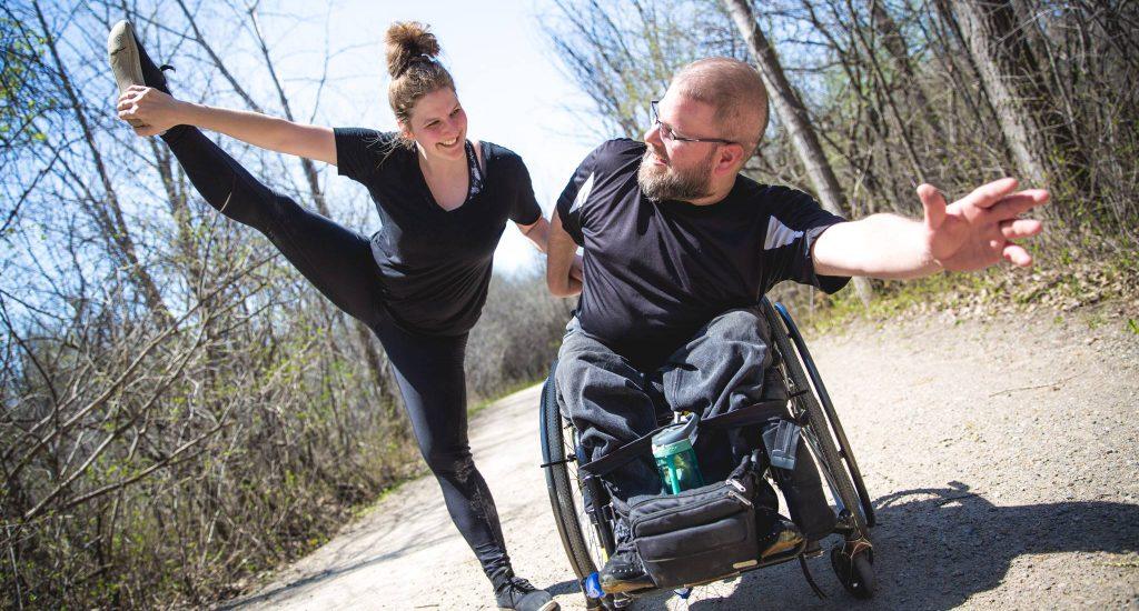 Marie Josée Raymand en train de danser avec un danseur en fauteuil roulant.