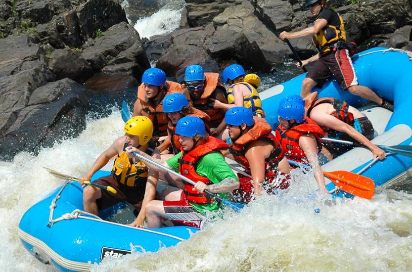 des jeunes dans une embarcation pneumatique font du rafting dans des rapides.