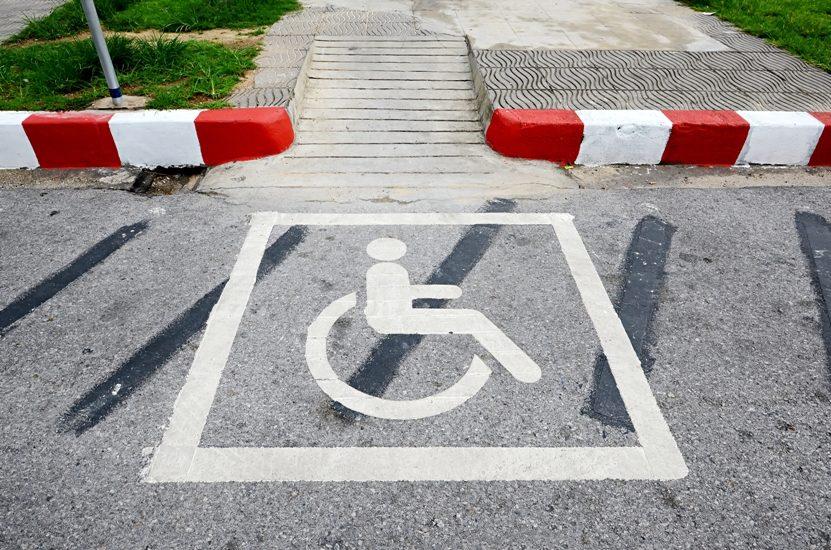 On voir au sol un symbole de stationnement pour personne en fauteuil roulant et plus haut une barrière comme celles des passages à niveau.