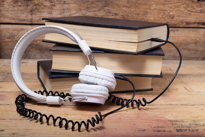 On voit une pile de livres dans lequel sont branchés des écouteurs blancs avec un fil noir.