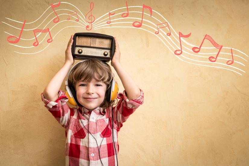 Une petit garçon tient une radio sur sa tête et il en sort une portée musicale et des notes roses et blanches.