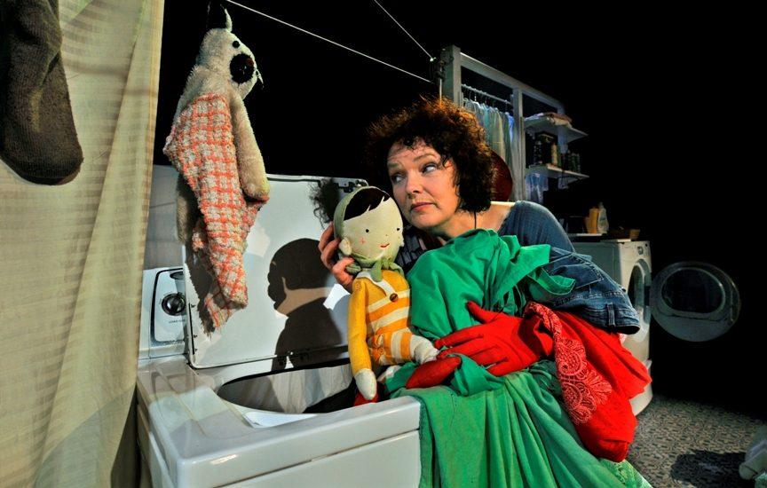 On voit la comédienne, près d'une machine à laver, qui tient une poupée.