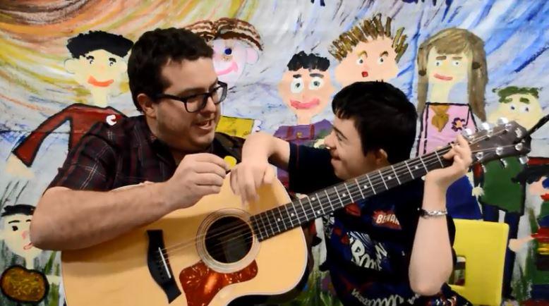 Le guitariste du groupe Les campagnards, initie un élève de l'école à la guitare.