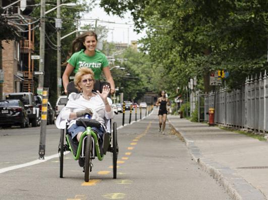 Une femme est dans un fauteuil Kartus et derrière, une jeune femme court en poussant le fauteuil.