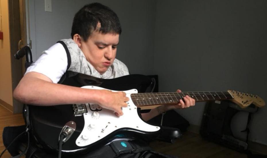 Un jeune homme en fauteuil roulant apprend à jouer de la guitare électrique.