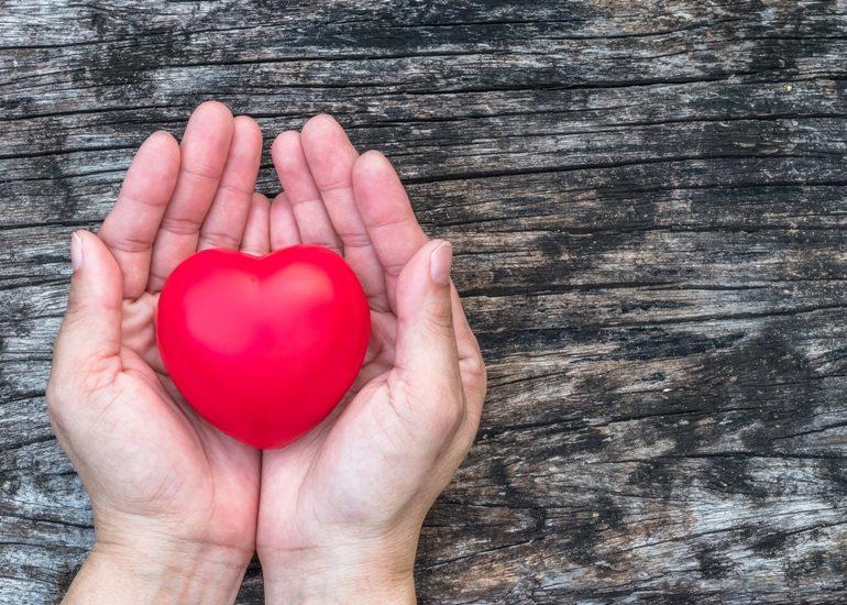 """sur un fond """"planche de grange"""" des mains tiennent un beau coeur rouge"""