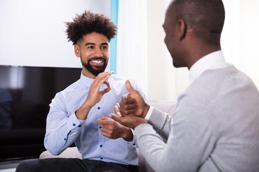 Deux hommes noirs conversent en langue des signes (probablement américaine)