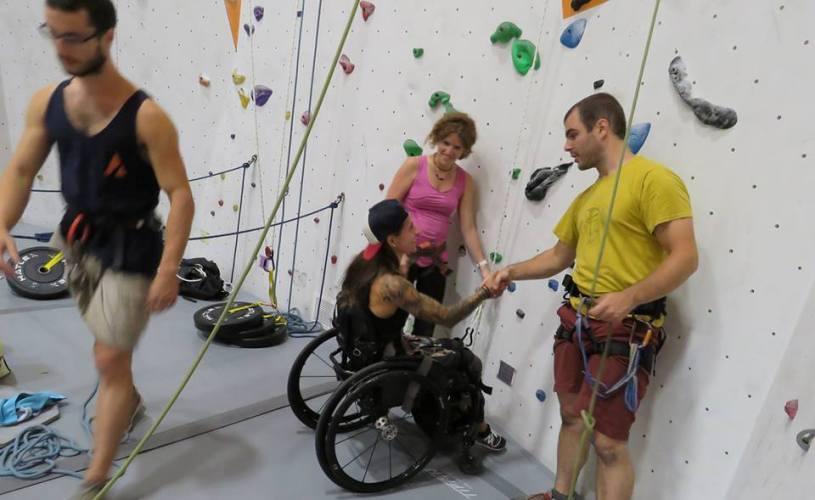 Devant un mur d'escalade, on voir deux personnes debout qui tendent la main à une femme en fauteuil roulant.
