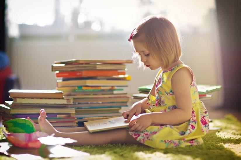 une fillette qui porte une robe jaune lit un livre. Elle est assise par terre à côté d'une pile de livres.