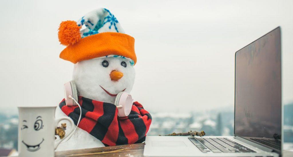 Un bonhomme de neige portant des écouteurs au cou est assis devant une table avec un ordinateur portable et une tasse.