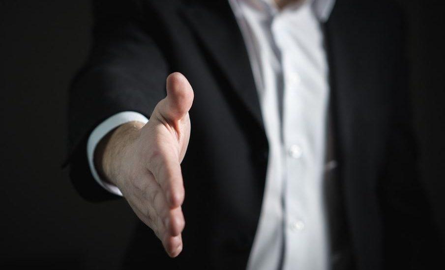 Un homme,dont on ne voit pas la tête, veston nour et chemise blanche, tend la main.