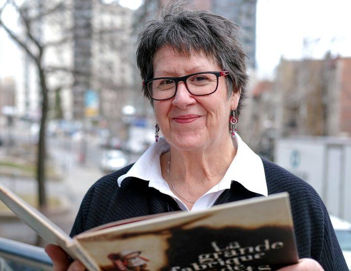 Marie Lalande, tenant un livre jeunesse, devant une fenêtre donnait sur le centre-ville de Montréal