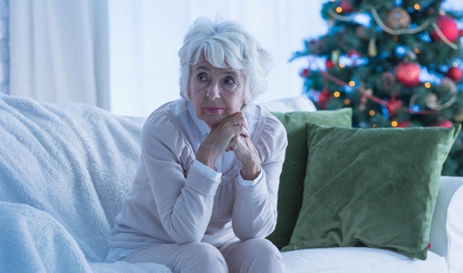 Une dame aux cheveux blancs est assise sur un sofa et a l'air triste, la tête appuyée sur ses mains jointes. Derrière elle un sapin décoré.
