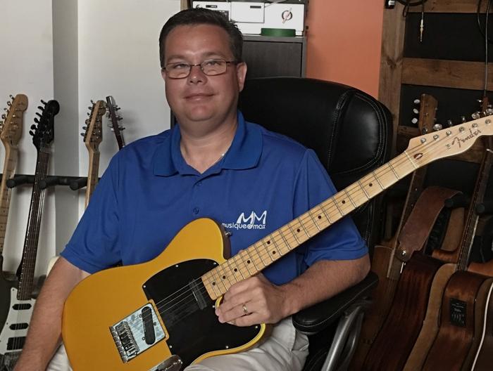 Tommy Théberge est assis sur une chose chaise de cuir noire et tient dans ses mains une guitare électrique. Il est photographié à l'école Musique O Max.
