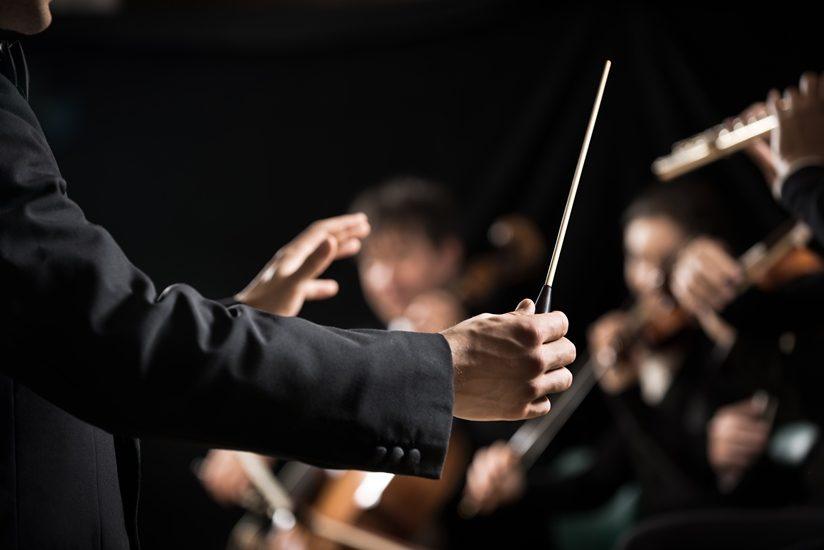 On aperçoit laman d'un chef d'orchestre et plus loin, quelques musiciens.