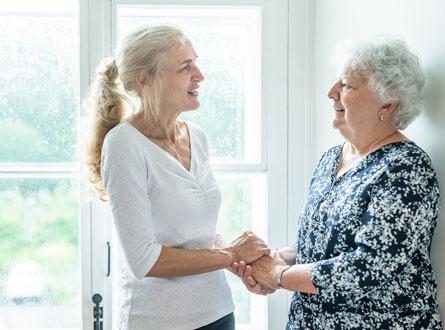 Une femme aux cheveux blonds atiens la mains d'une dame âgée au cheveux gris. Derrière elles une fenêtre au châssis blanc.