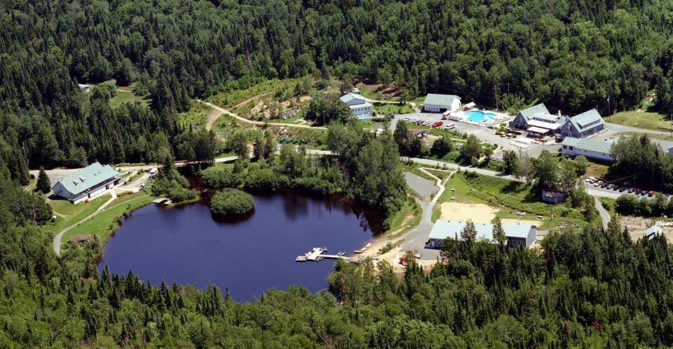 Vue aérienne du camp, situé près d'un lac.