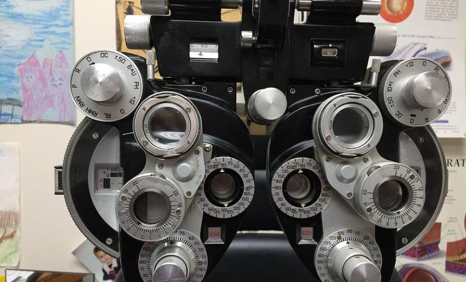 Un appareil pour examiner les yeux, dans un classe avec des dessins d'enfants au mur.