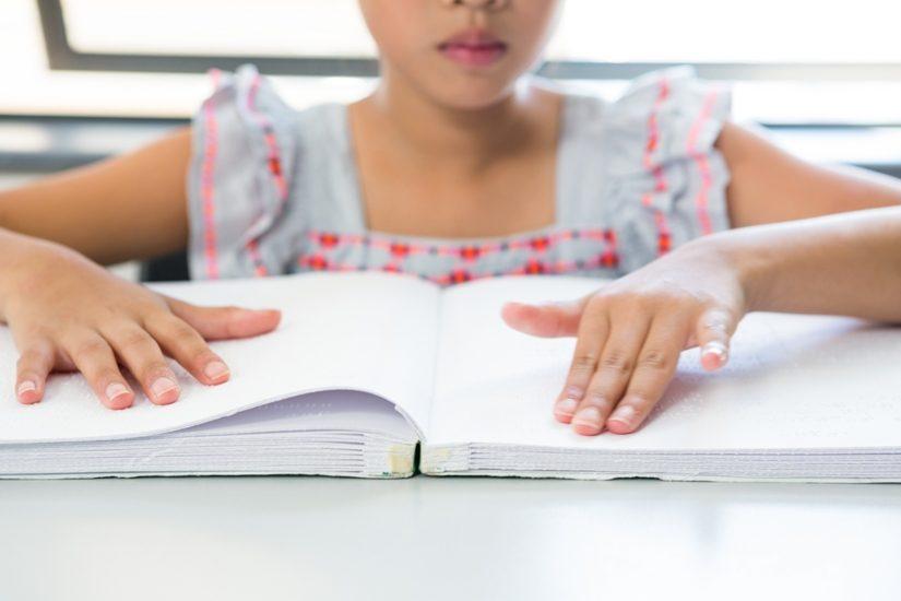 Une fillette lit dans un livre en braille.