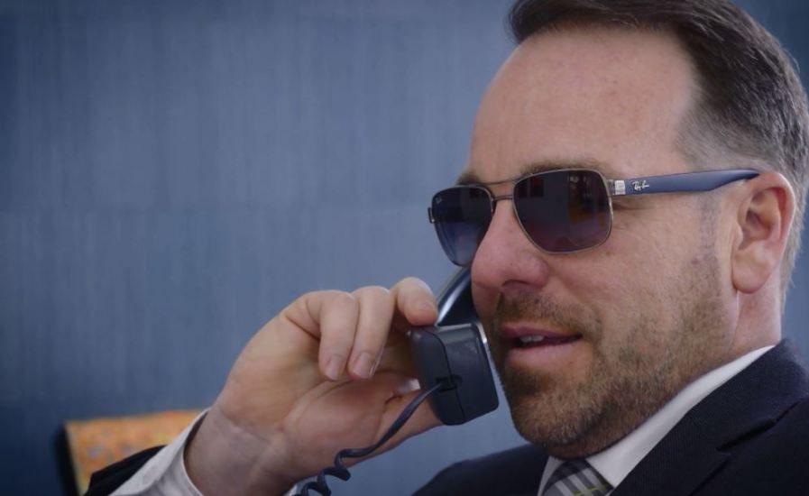 Gabriel Couture, un homme au cheveux court brun avec des verres fumés, parle au téléphone.